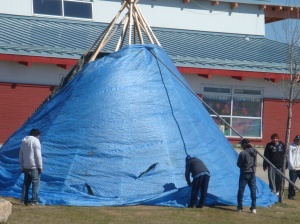 Use a pole to push the tarp up the tipi and hold it in place until you fasten the ties in place.